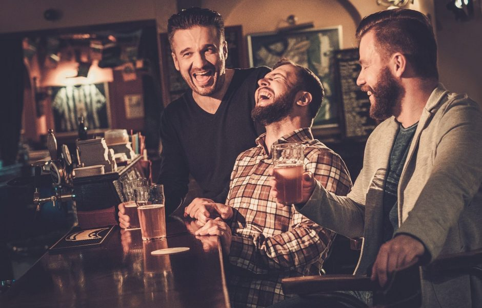 Friends laughing and drinking beer at a pub